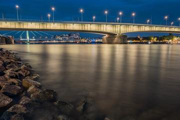 Deutzer Brücke während der blauen Stunde bei Nacht mit den Kranhäusern und der Severinsbrücke im Hintergrund, im Vordergrund Steine