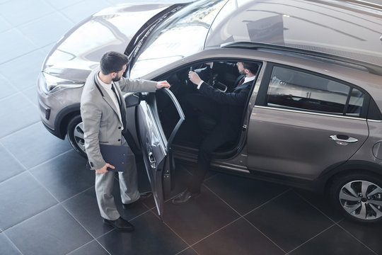 Full length high angle view at bearded car salesman opening door for customer getting into his brand new luxury car, copy space