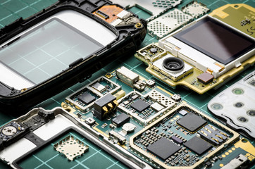 Microchips, semiconductor components and precious metals on the Board of the disassembled old mobile phone close-up on a green background