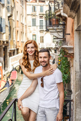 young beautiful couple, a girl with red hair and a white dress and a man in a white T-shirt are standing on a balcony in the beautiful city of Venice in Italy