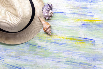 Straw hat and seashells on colorful wooden with travel or vacation concept.