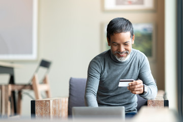 Happy mature man holding credit card paying online by using laptop for payment. Asian senior male smiling shopping online with omni channel concept at coffee shop. Retired man with urban lifestyle.