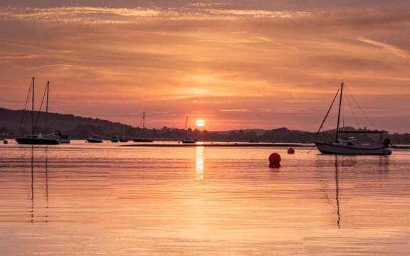 Sunset over River Exe Estuary at high tide with reflections of yachts