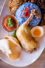 Nasi Lemak is a Malay fragrant rice dish cooked in coconut milk and butterfly pea served with fried chicken, fried small fish, roasted peanut, boiled egg and krupuk.