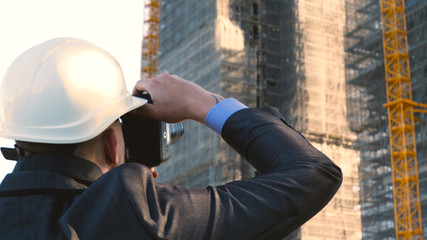 Portrait of a successful young handsome engineer, architect, builder, businessman, wearing a white helmet, in a suit, doing selfie, skyscraper background and building.