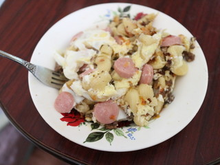 Fried eggs, sausages, potatoes in a plate
