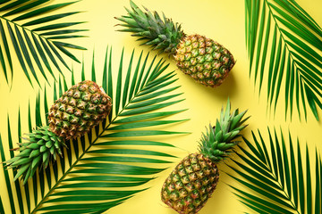 Pineapple and tropical palm leaves on yellow background. Top view. Summer concept. Creative flat lay with copy space.