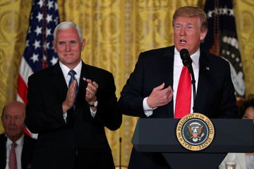 U.S. President Donald Trump, next to Vice President Mike Pence, delivers remarks at a meeting of the National Space Council at the White House in Washington