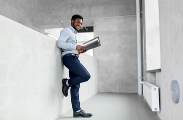 business, people and corporate concept - smiling african american businessman with folder at office
