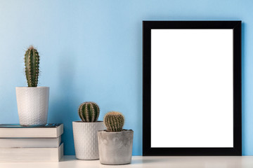Mockup with a black empty frame with a white center on a background of a blue wall with a decoration of cactuses and three books