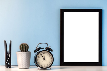 Mockup with a black empty frame with a white center against the background of a blue wall with a black alarm clock, cactus and oversizde clothes peg