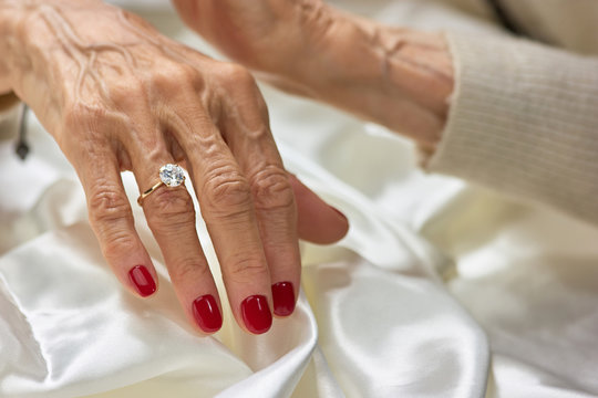 Female aged hand with diamond. Senior woman hand with red manicure wearing golden ring with diamond.
