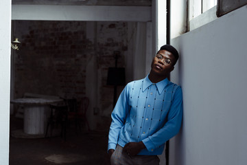 Stylish black man leaning on wall