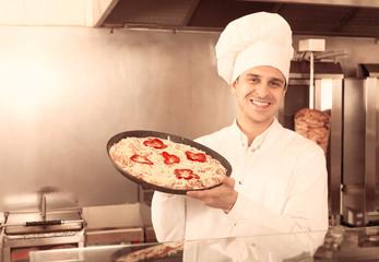 Male chef with Italian pizza at bistro.