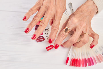 Red manicure and red nail sample. Old woman hands with red manicure in nail studio. Collection of bright nail color samples.