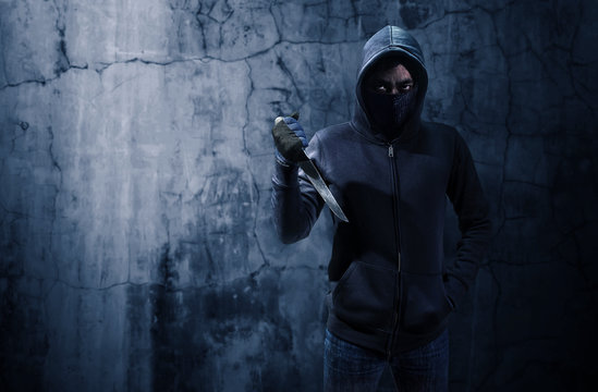 Criminal or bandit holding a knife. Empty space for text or draw