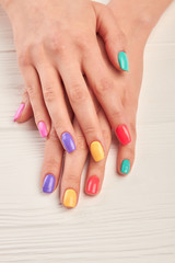 Aluminium Prints Manicure Well-groomed hands with summer manicure. Young woman nails covered with different colors polish on white wooden background. Perfect summer manicure.