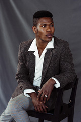 Stylish black man sitting on chair