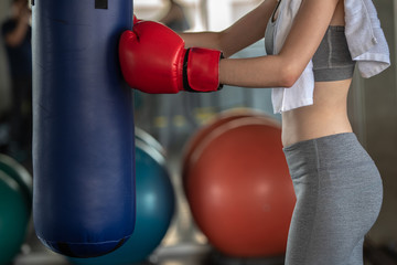 Portrait photo about  body of cute Asian sports girl in red boxing gloves and big punching bag at indoor sport gym, beauty and healthy sport concept.
