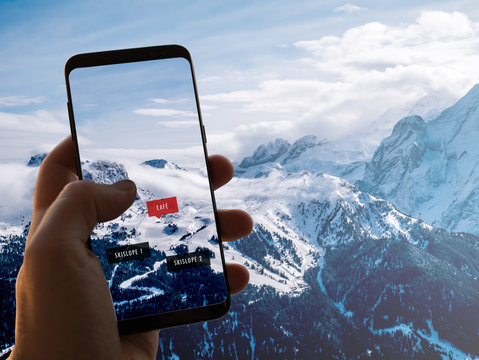 Augmented Reality (AR) information technology is displayed on a smartphone in the alps to guide and show information about café, ski slopes and restaurants on the screen. Hand is holding mobile phone.