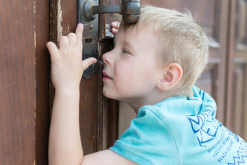 the child peeps through the keyhole.