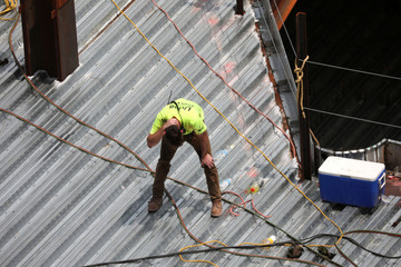 A construction worker holds ice on his neck while working on a sheet metal roof during very hot weather in the Harlem section of Manhattan in New York City