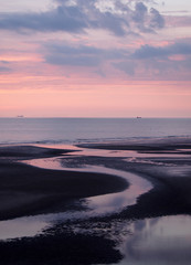 beautiful purple twilight over a calm sea with water on the beach reflecting colorful sunset clouds