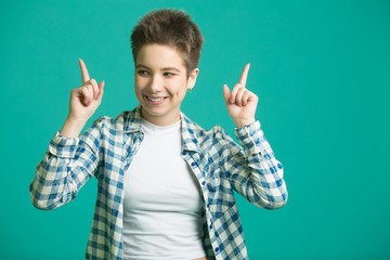 beautiful young girl with short hair in a shirt on a blue background pointing with her finger