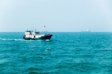 Small old fishing boat with Chinese flag in South China Sea near Hong Kong. Large container ship with cranes in haze on horizon line. Sunny summer day. Fishing industry.
