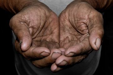 The poor old man's hands beg you for help. The concept of hunger or poverty. Selective focus.
