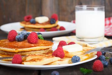 Classic american breakfast, homemade  pancakes with fresh berries, honey and glass of milk