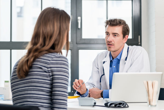 Young devoted doctor holding an X-ray while listening with attention to his female patient during a private consultation in the office