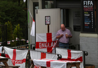 An England soccer fan checks his phone as he watches the team's first match in the World Cup against Tunisia at The Robin pub near Newcastle