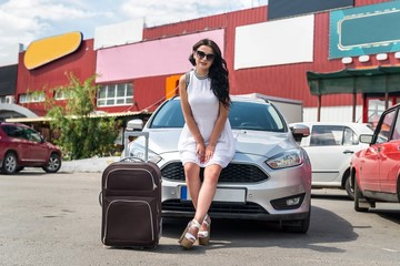 Woman with suitcase sitting on car bonnet