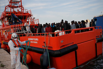 Migrants stand on a rescue boat upon arrival at the port of Malaga