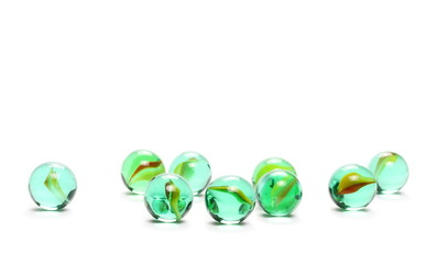 Pile of green glass marbles, isolated on white background