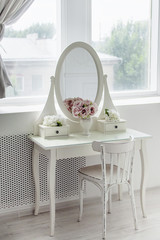 A beautiful white mirror on the table. Elegant bright interior.
