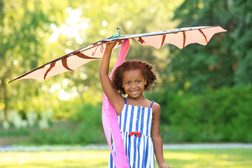 Cute African American girl playing with kite outdoors