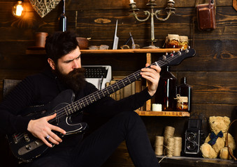 Best weekend. Man bearded musician enjoy evening with bass guitar, wooden background. Man with beard holds black electric guitar. Guy in cozy warm atmosphere play relaxing soul music