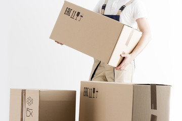 Close-up view of mover holding cardboard box isolated on white background. Concept o relocation into new house. Loader with boxes.