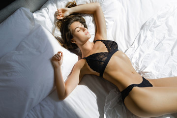 Young sexy woman in black lingerie lying on the bed