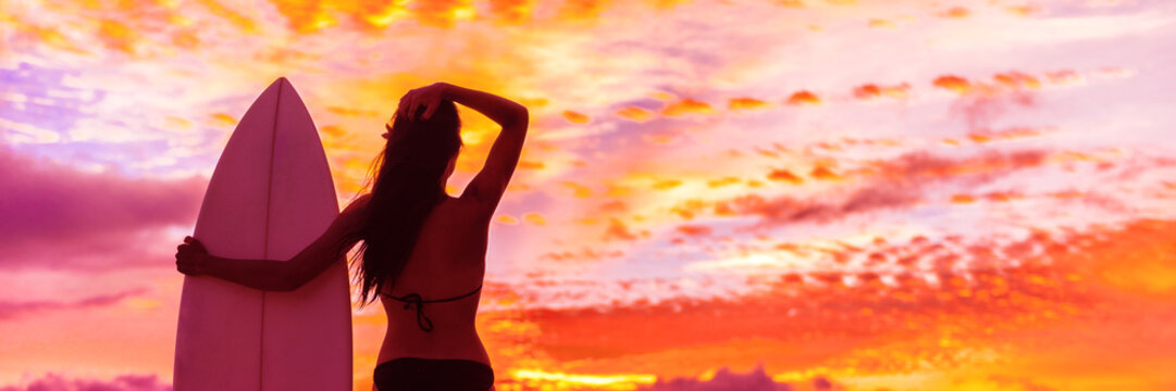 Hawaii surf summer vacation lifestyle. Silhouette of surfer woman at sunset with surfboard on beach. Banner panorama.