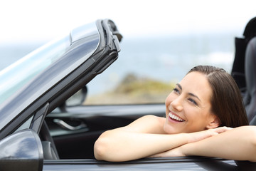 Happy driver enjoying vacations in a cabriolet car