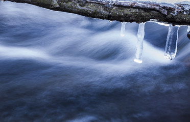 Abstract shot wintertime about some icicles in front of a cold stream, long exposure. Domorkapu, Hungary