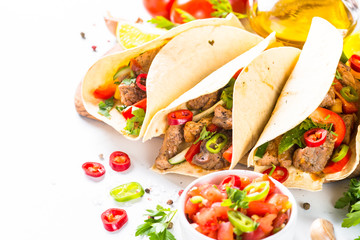 Mexican pork tacos with vegetables and salsa on white.