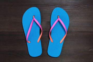 Blue flip flops isolated on wooden background. Top view