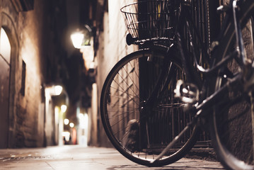 retro bicycle in the night old city on background bokeh light flare in night architecture, vintage bike in evening street in barcelona town, cycle transportation in backdrop building, travel concept