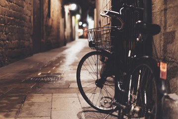 retro bicycle in the night old city on background bokeh light flare in night architecture, vintage bike in evening street in barcelona town, cycle transportation in defocus backdrop, travel concept