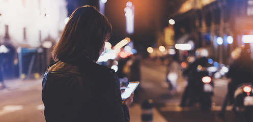 Fotomurales - Girl pointing finger on screen smartphone on background bokeh light in night city street, blogger hipster girl using in hands mobile phone, lights auto taxi; lifestyle online wifi internet concept