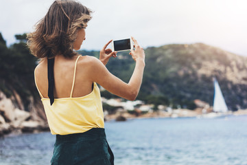 Hipster blogger girl holds mobile phone in female hands, take photo picture of natural seascape on a sunny summer day while travel and vacation, cellphone closeup on background ocean.